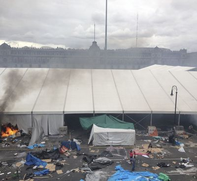 Riot police destroy the teachers' camp in Mexico City's zocalo in September 2013, leaving remnants of the tent city strewn throughout the square.